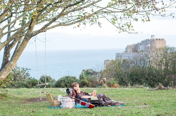 couple relaxing with a gorey castle and sea in the background in jersey channel islands